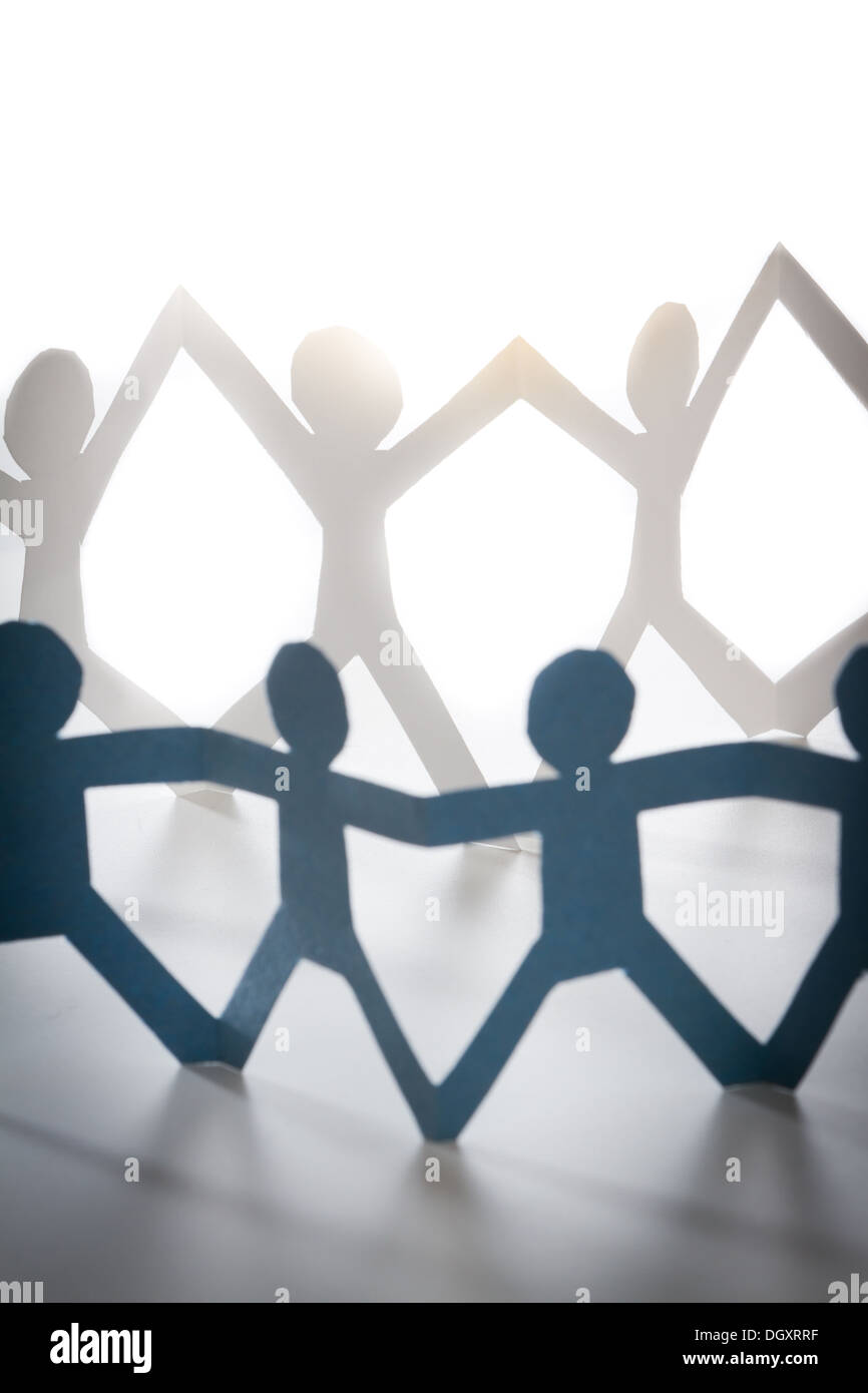 paper cutout of people. concept of people coming together and working as a team - Stock Image