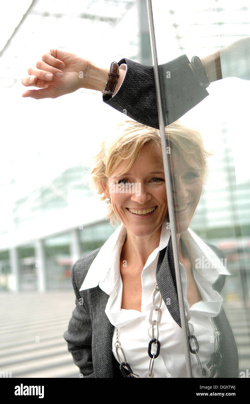 Businesswoman, 40-50, leaning against a glass wall - Stock Image