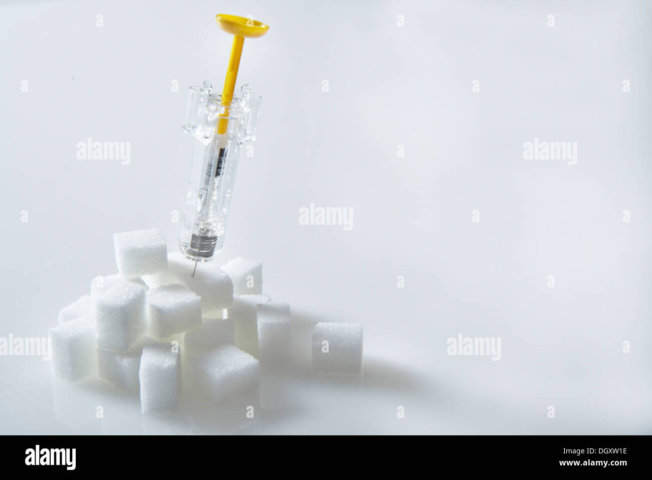 Syringe filled with insulin, insulin injection sticking in a pile of sugar cubes - Stock Image