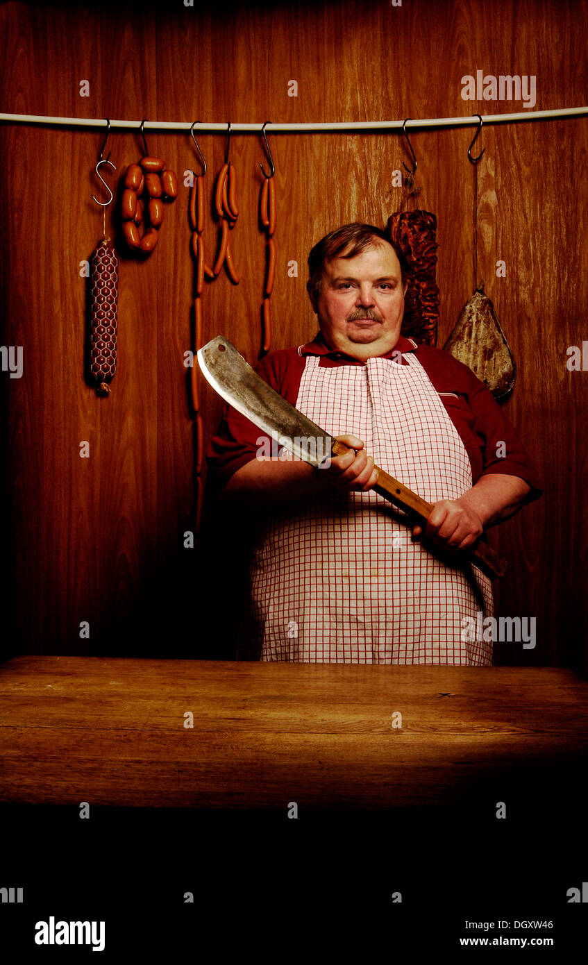 Fat butcher holding a meat cleaver in a butcher's store with a wooden ambience - Stock Image