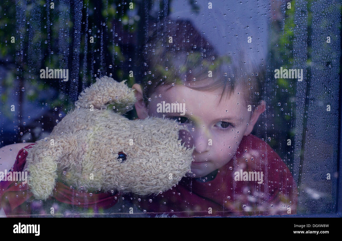 Boy looking dreamily out of a window with water drops, holding a stuffed animal in his arms - Stock Image