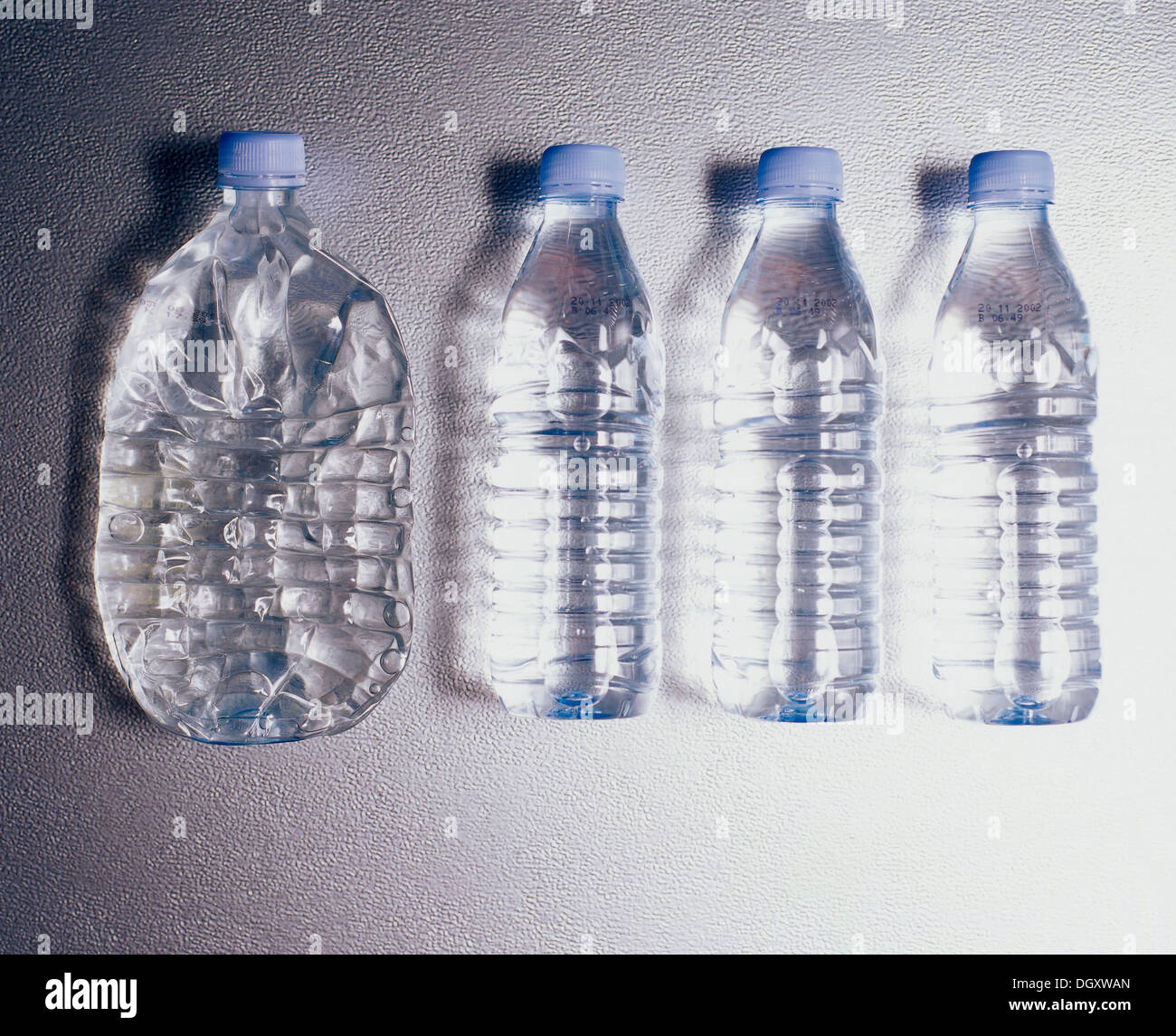 Row of plastic bottles, one flattened by being driven over - Stock Image