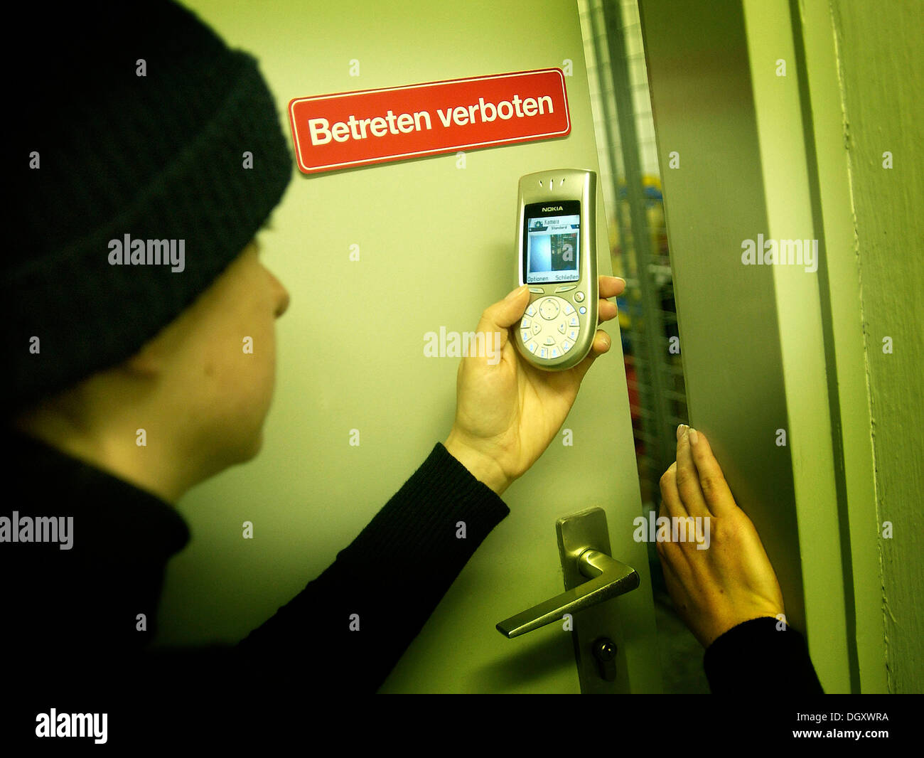 Burglar using a camera phone to take a photograph through the gap of a door, symbolic image for industrial espionage Stock Photo