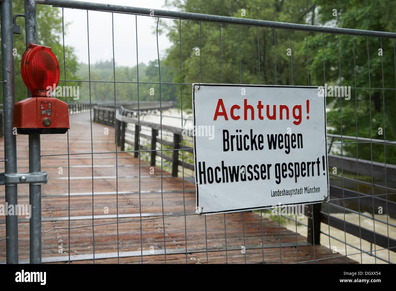 Barrier with a warning sign, 'Achtung! Brücke wegen Hochwasser gesperrt!', German for 'Attention! Bridge closed due to - Stock Image