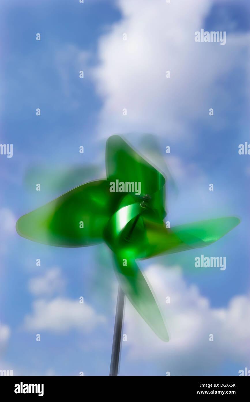 Green pinwheel rotating in the wind - Stock Image