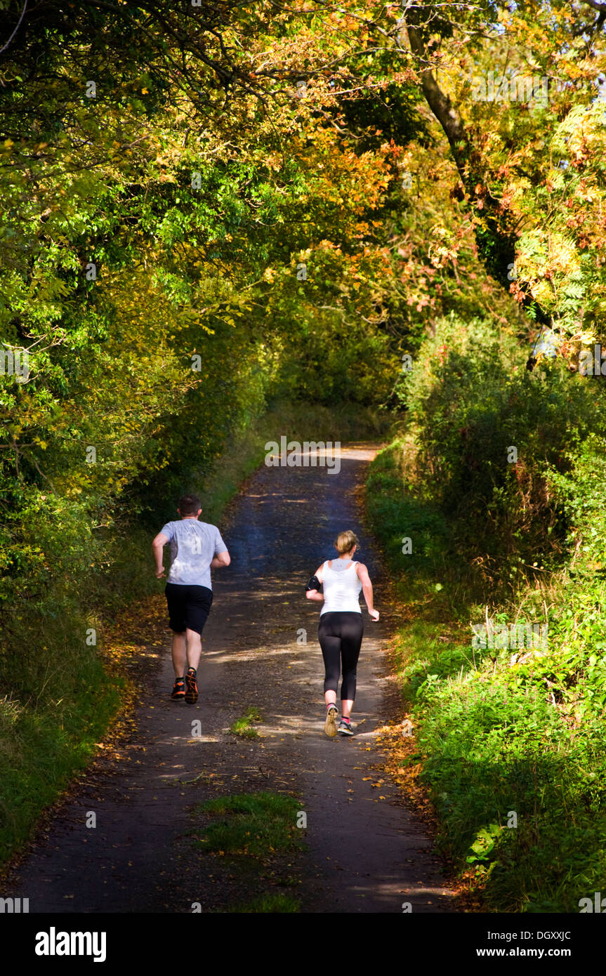 Two joggers man and woman running jogging down a rural Somerset lane - Stock Image