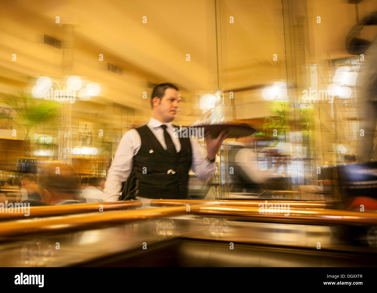 French waiter holding a tray rushing through a bar restaurant in Paris - Stock Image