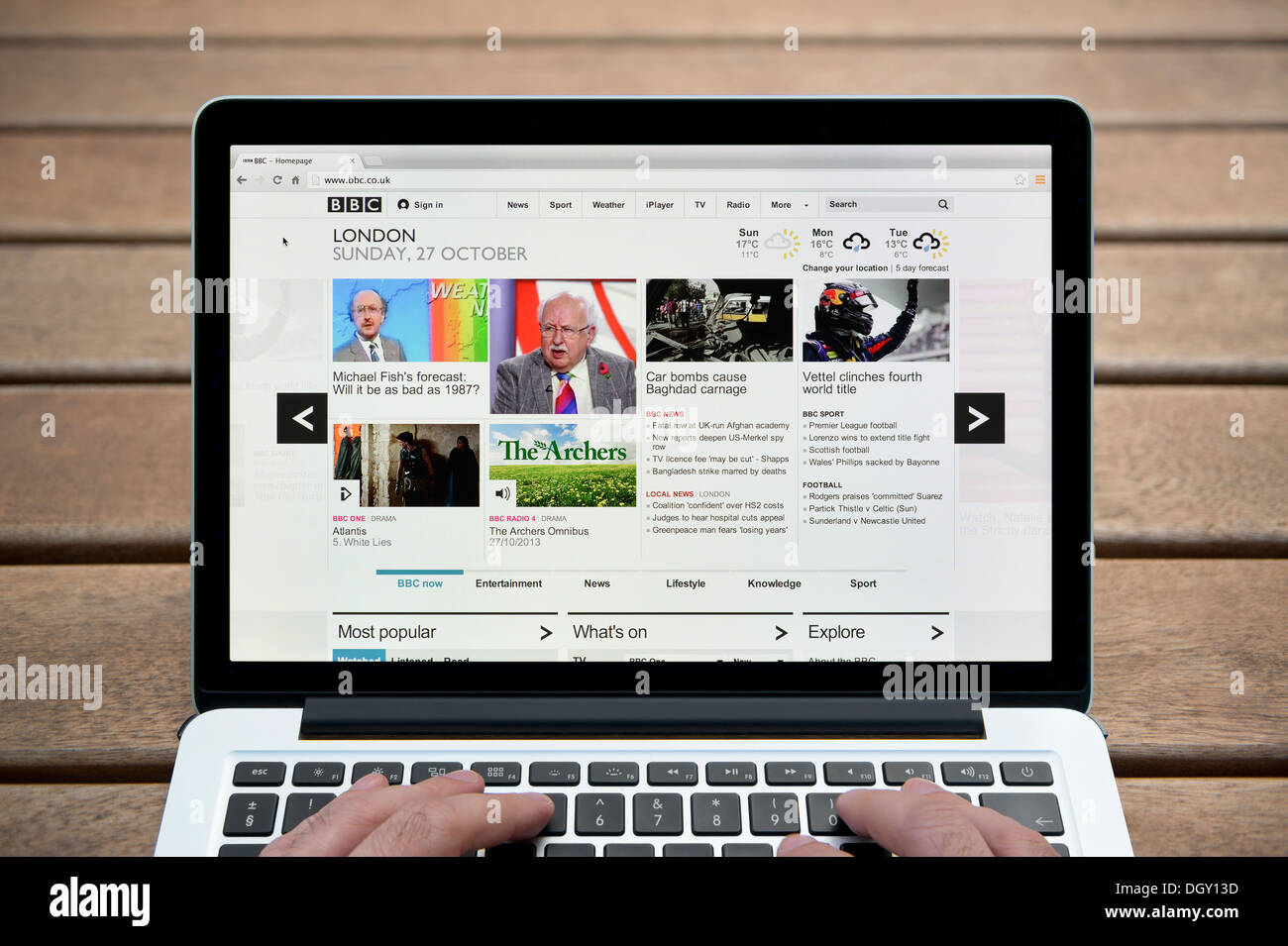 The BBC Online website on a MacBook against a wooden bench outdoor background including a man's fingers (Editorial use only). - Stock Image