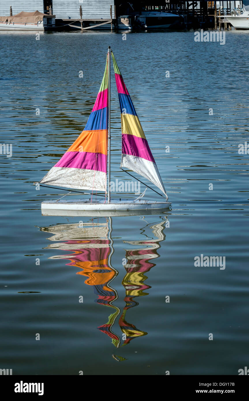 Scale model of a sloop sail boat with multi-colored striped sails floating on Lake Dora in the harbor of Mount Dora, Florida. - Stock Image