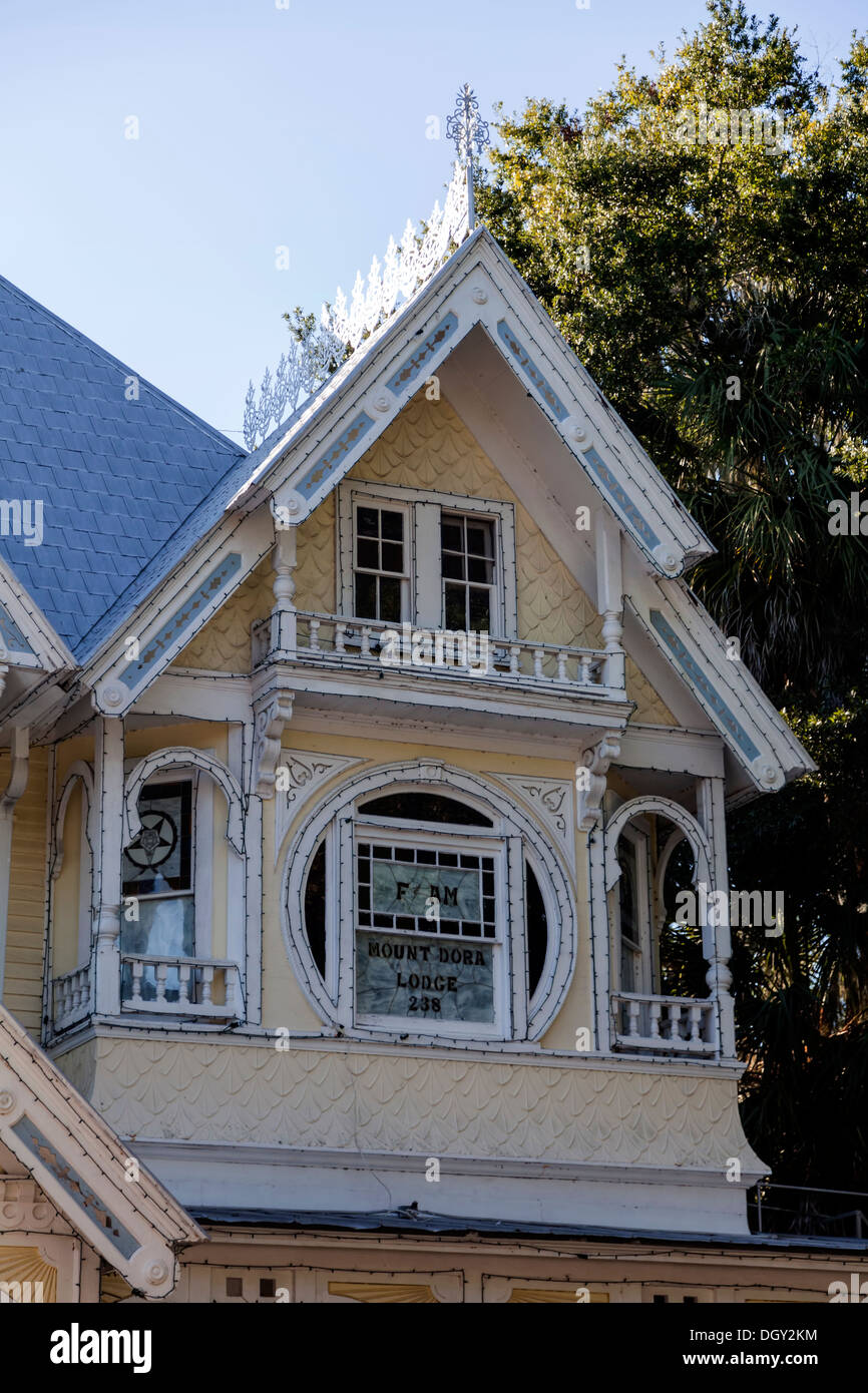 Victorian house gable end windows and wall detail with round window, gingerbread wood trim and moldings. - Stock Image
