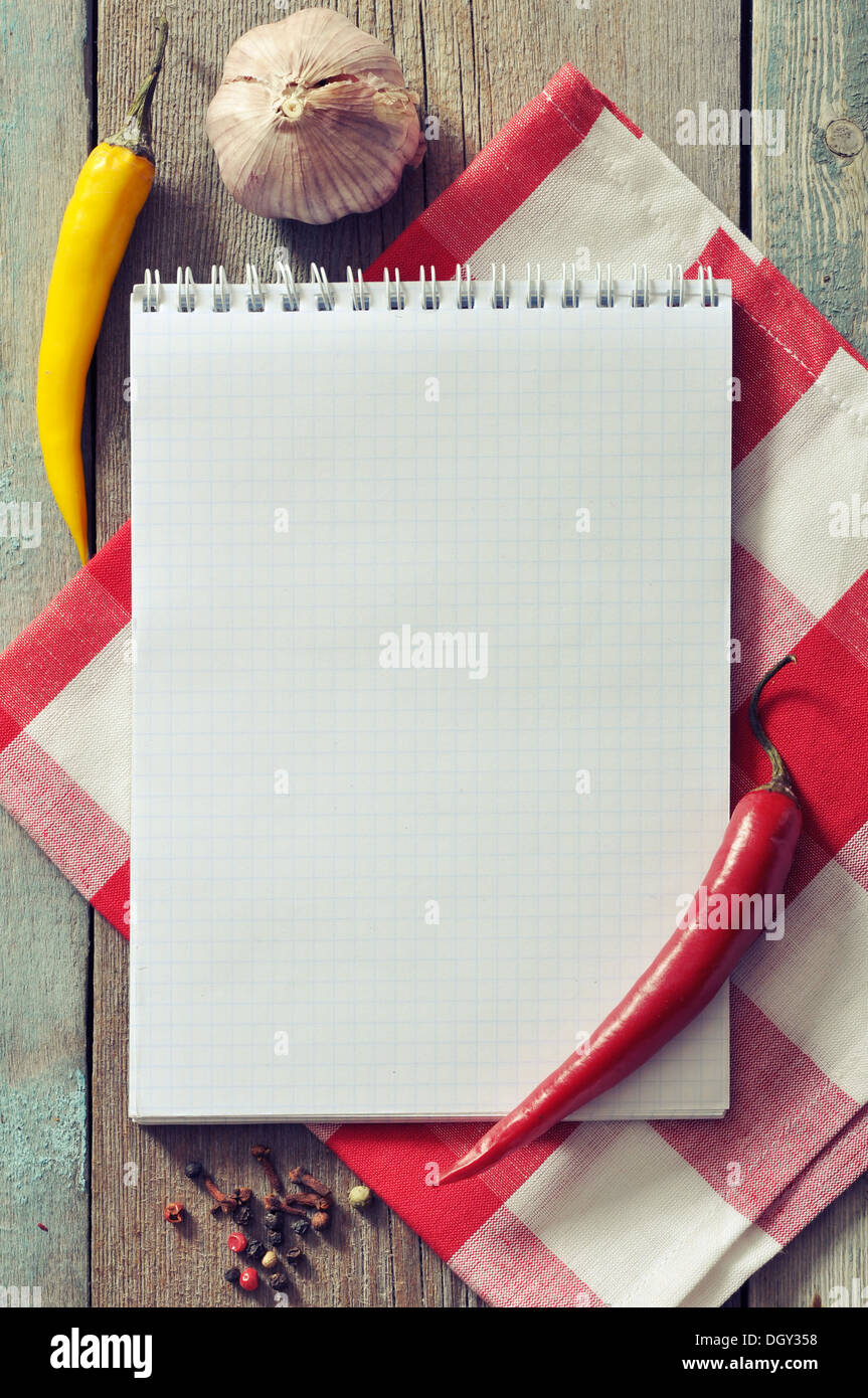 Blank recipe book with kitchen towel on wooden background - Stock Image