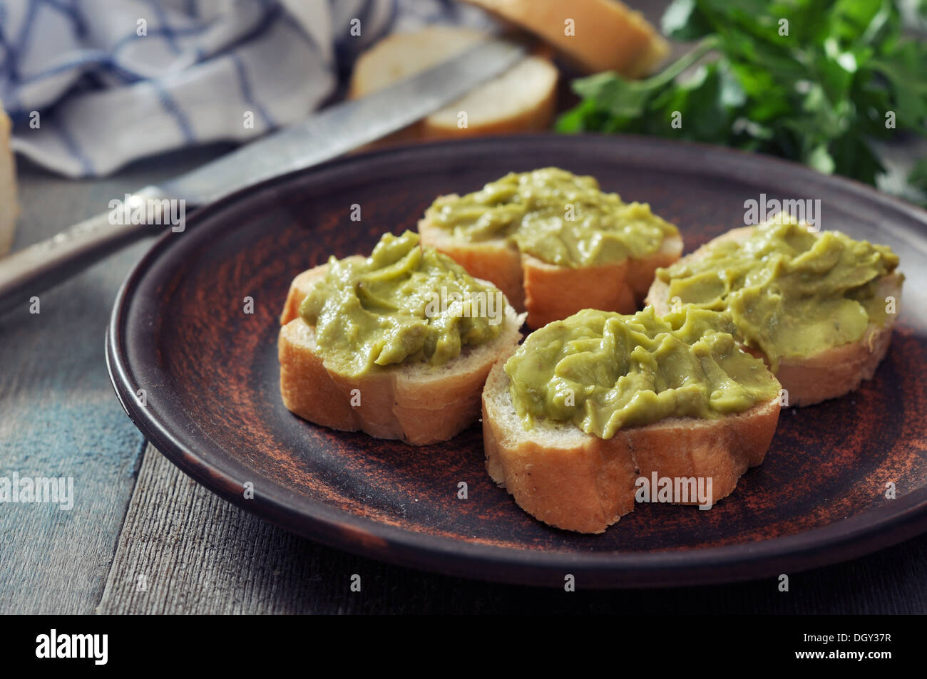 Delicious appetizer canapes of bread and guacamole served with parsley closeup - Stock Image