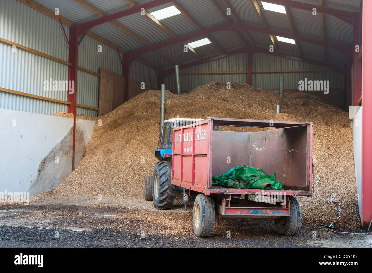 biomass storage shed with tractor and trailer - Stock Image