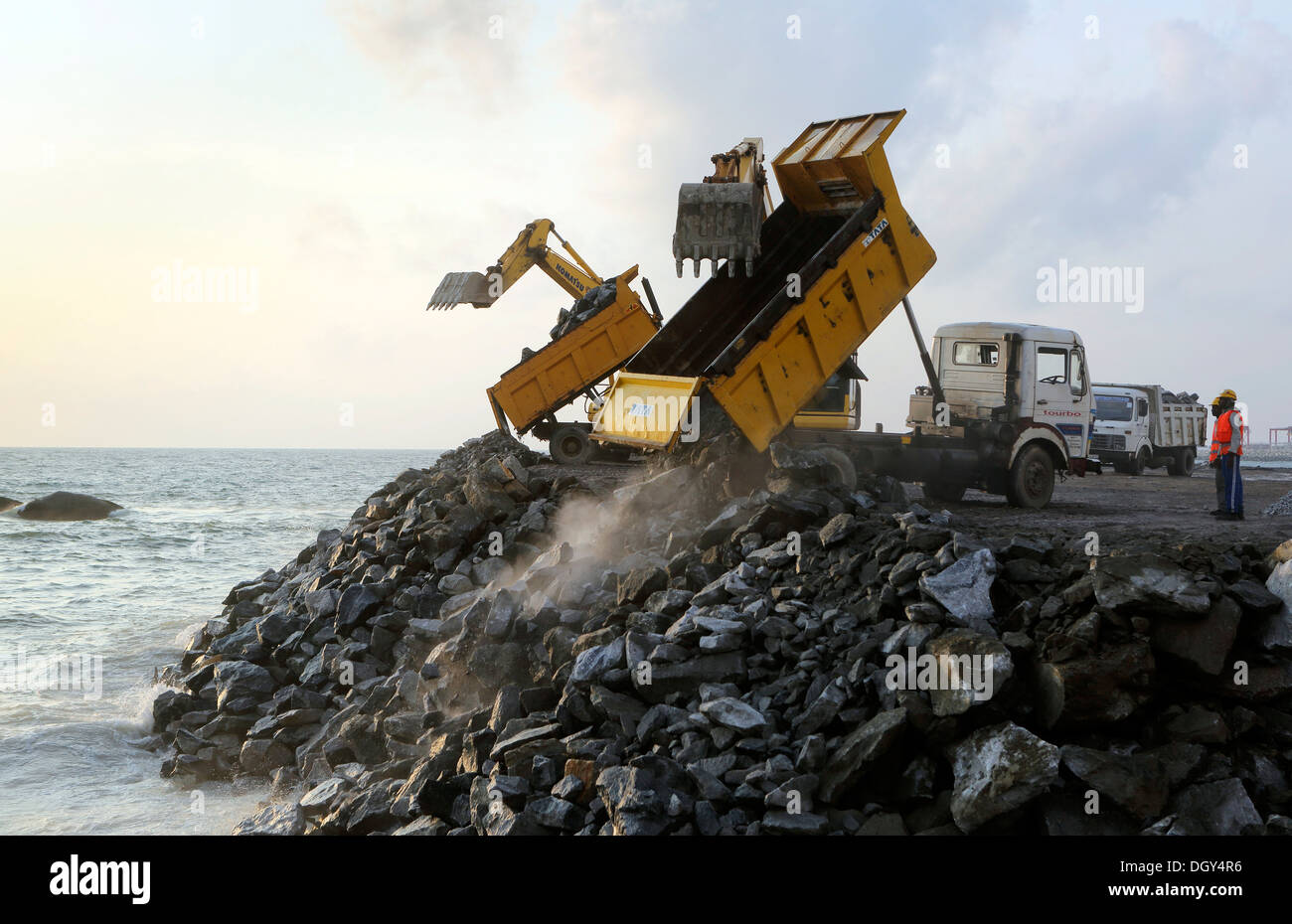 Dump truck offloading large rocks onto a sea wall barrier in Colombo, Sri Lanka - Stock Image