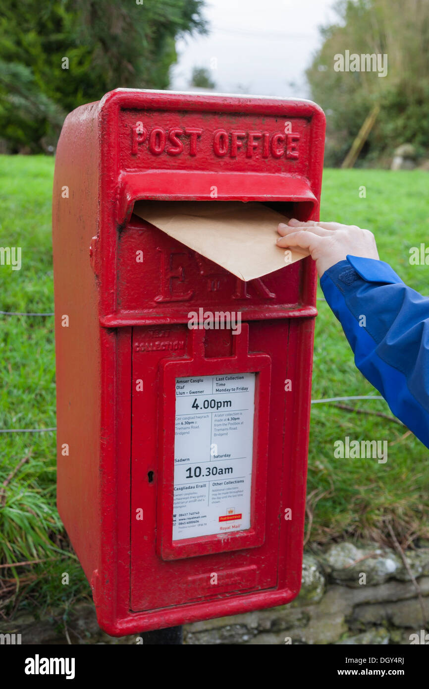 posting letter in traditional red post office box - Stock Image