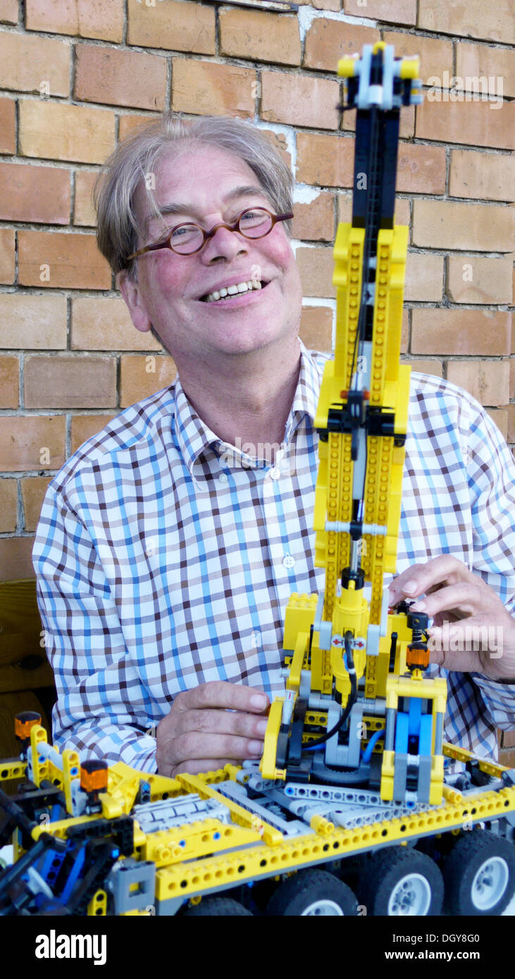 Active, senior technology enthusiast enjoying his hobby and demonstrating his self-built crane - Stock Image