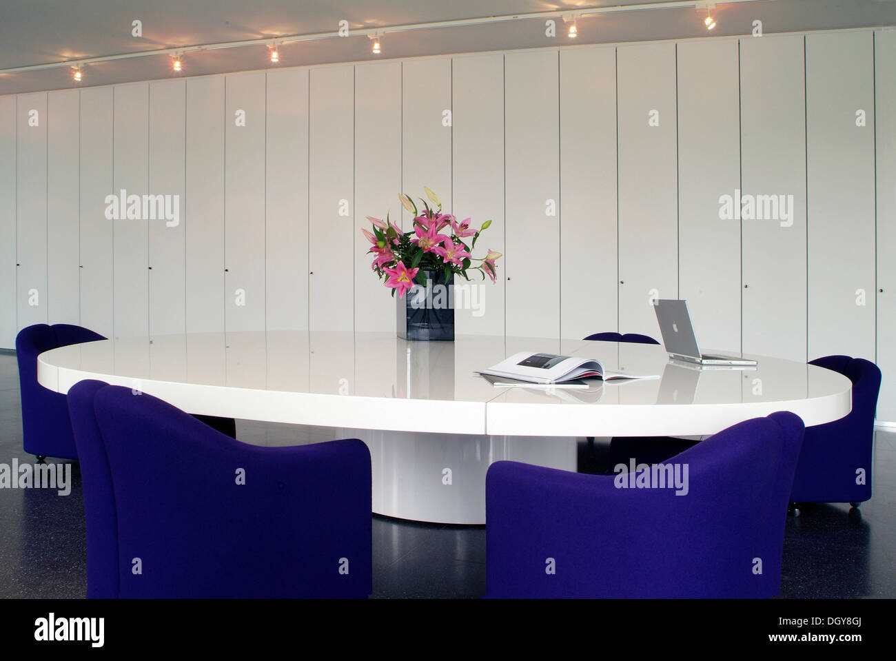 Oval Conference Table With A Laptop And Chairs In A Modern Design In - White oval conference table
