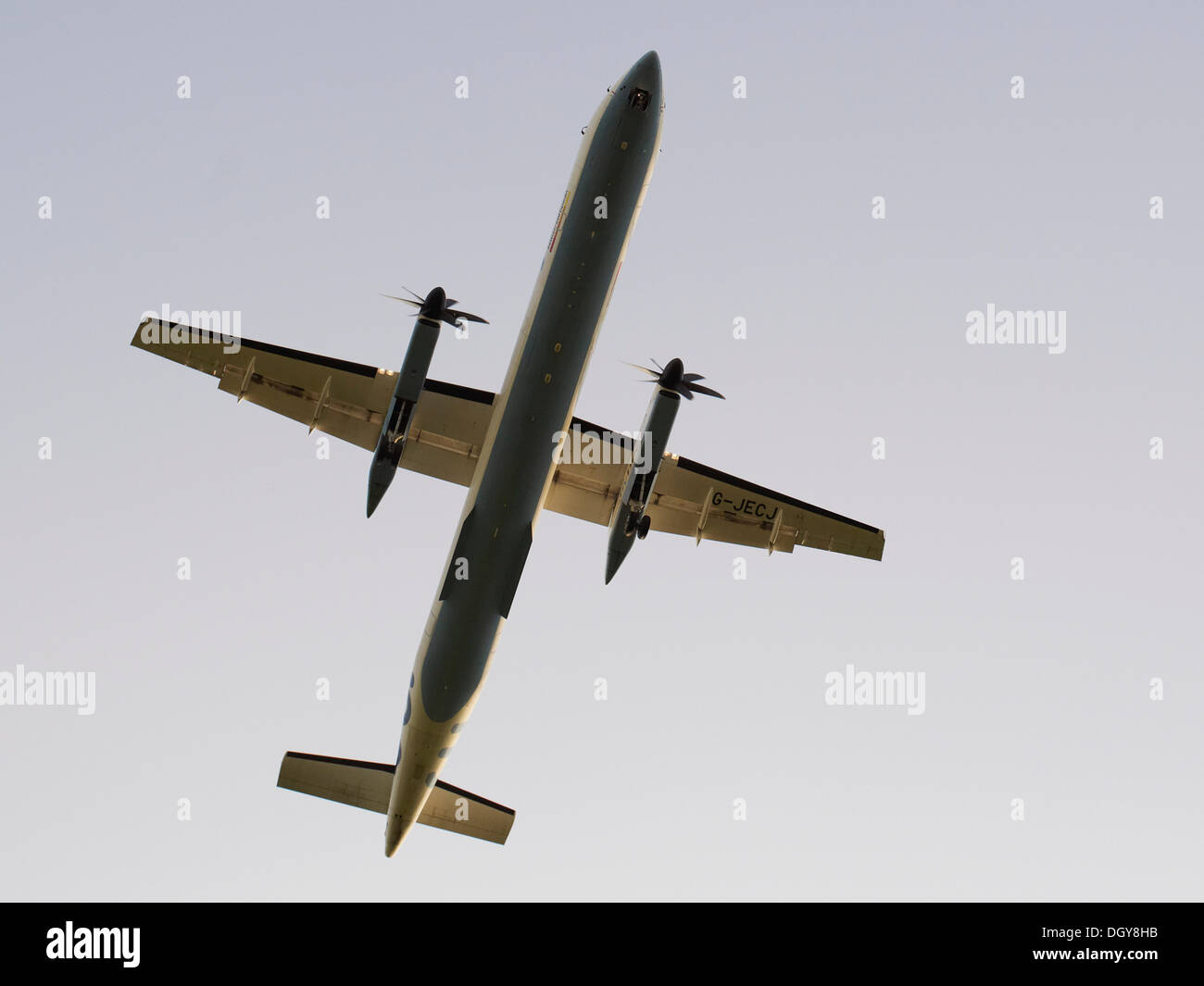 Twin engine turboprop aircraft of British European airline viewed from below on landing approach, Frankfurt Airport - Stock Image