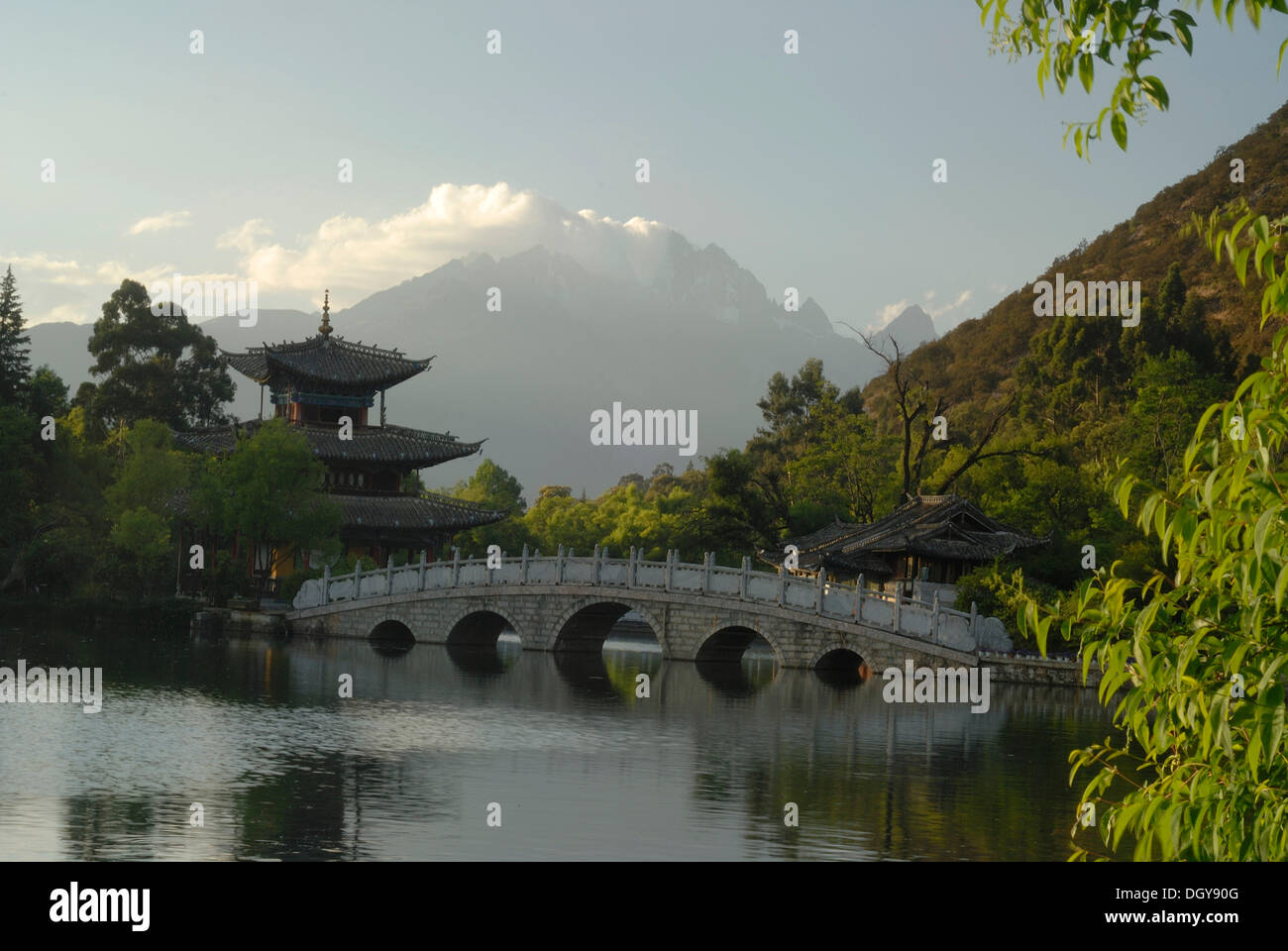 Pagoda, pavilion and Chinese bridge in the Black Dragon Pool Park, in the back the Jade Dragon Snow Mountain, 5596m - Stock Image