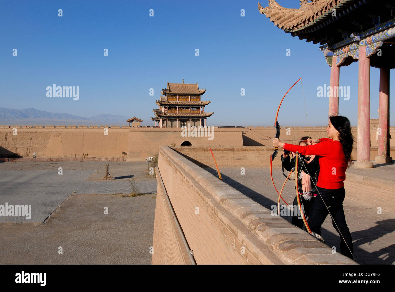 Chinese woman using a bow and arrow at the Jiayuguan Fortress with two gatehouses at the western end of the Great Wall of China - Stock Image