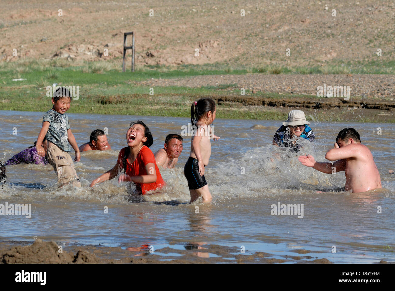 Bathing children and adults of a Mongolian extended family, splashing each other with water in the Ongi river, Oemnoegov Aimak - Stock Image