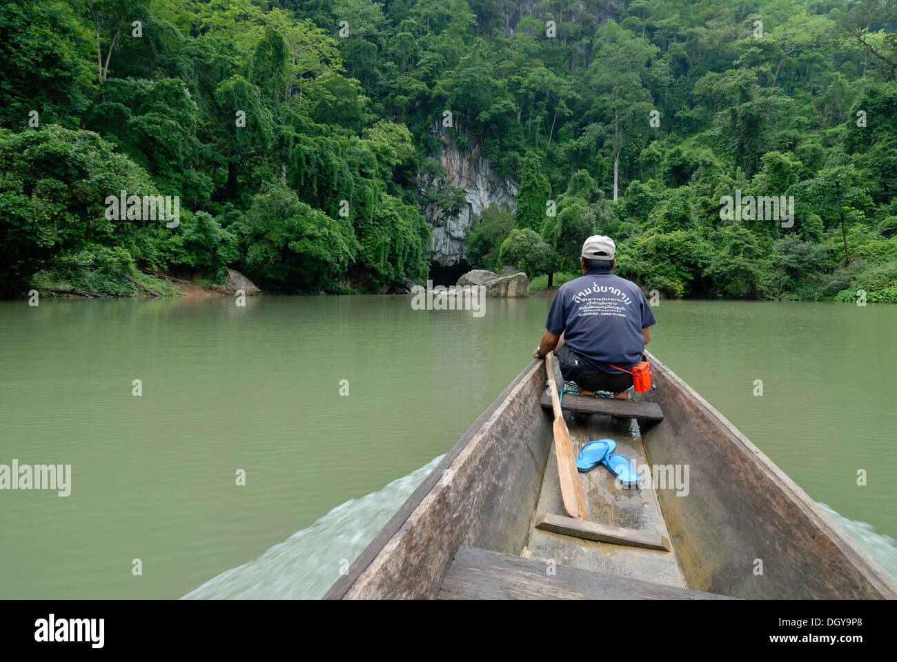 Laotian man with a simple long boat at the entrance of the 7.5 km long cave of Tham Kong Lor, in the dense tropical rain forest - Stock Image