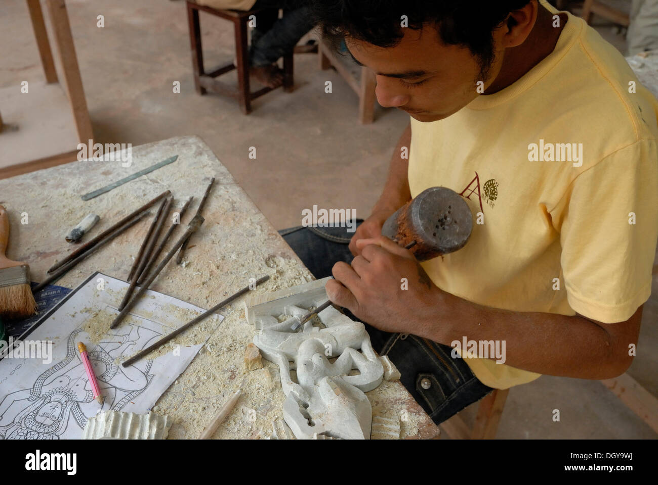 Young Cambodian artisan during the artistic craftsmanship of stone with a wooden hammer and a chisel to produce a traditional - Stock Image