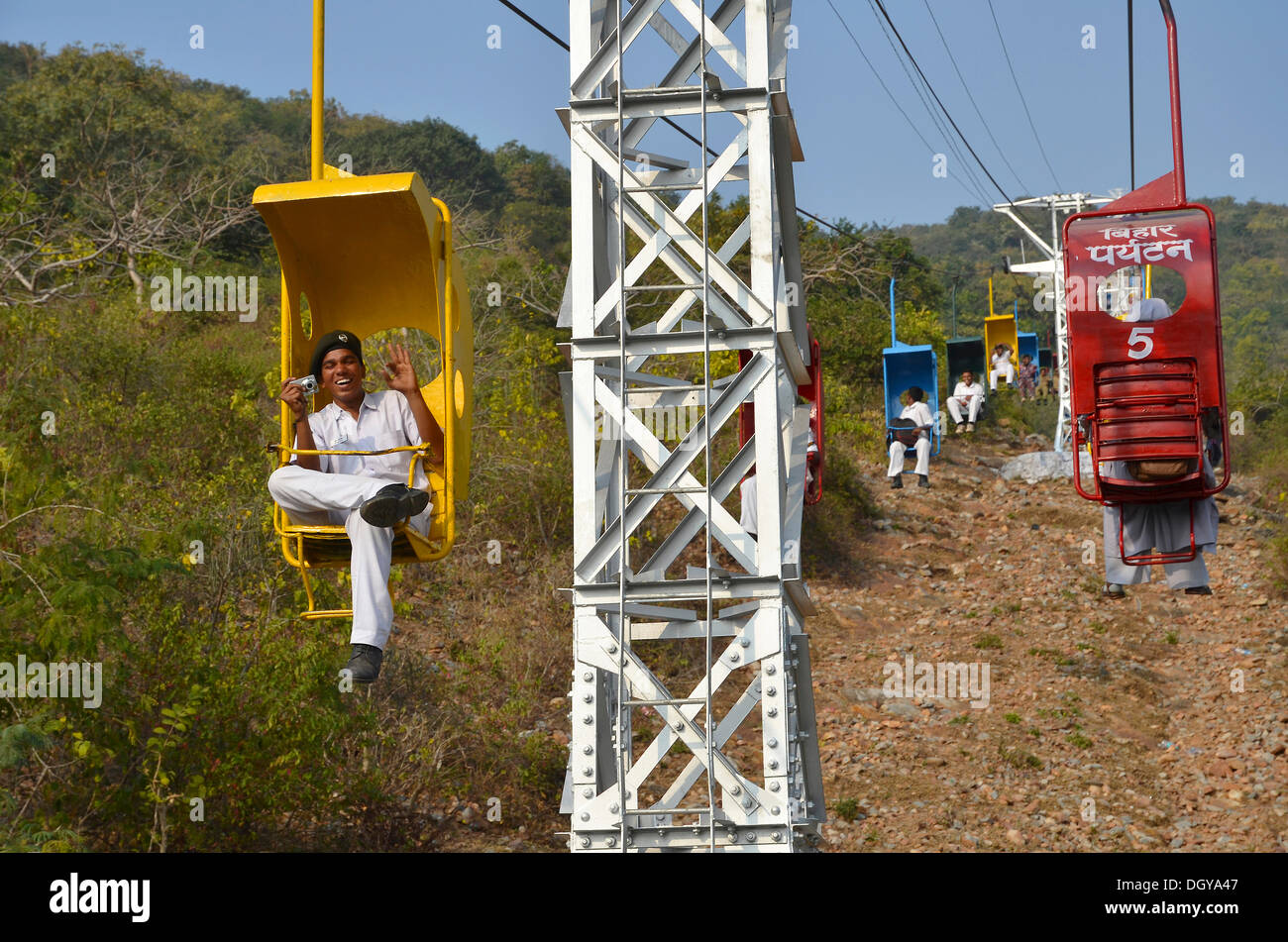 Cable car, chairlift, Indian man and woman sitting in brightly painted one-person chairlifts at Vulture Peak Stock Photo