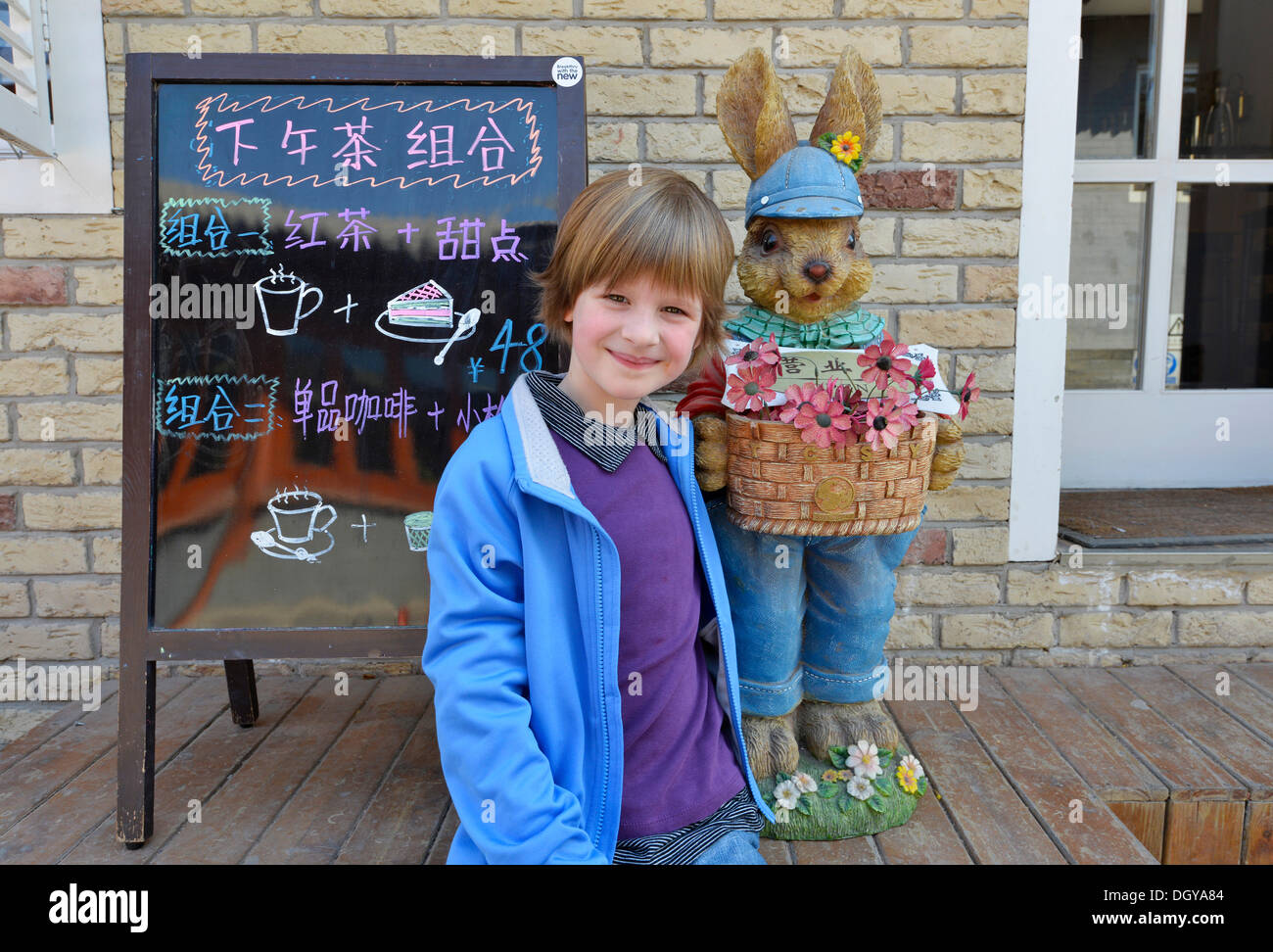 Girl, 6, in front of the Easter bunny in an old traditional hutong, a traditional residential courtyard, in Beijing, China, Asia - Stock Image