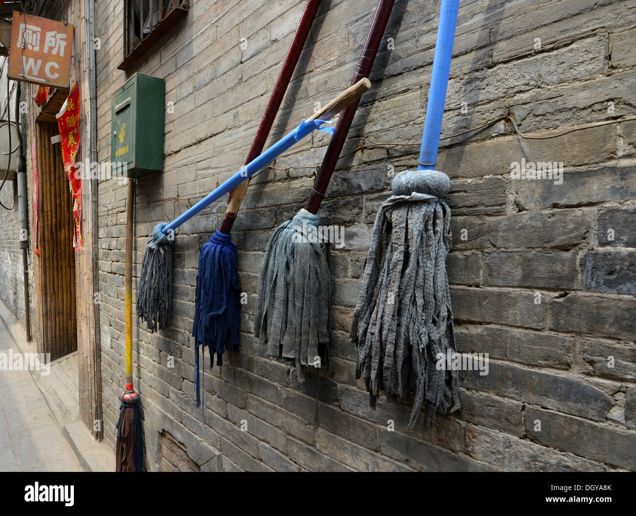 Mops outside a Chinese toilet block, historic city centre of Pingyao, Shanxi, China, Asia - Stock Image