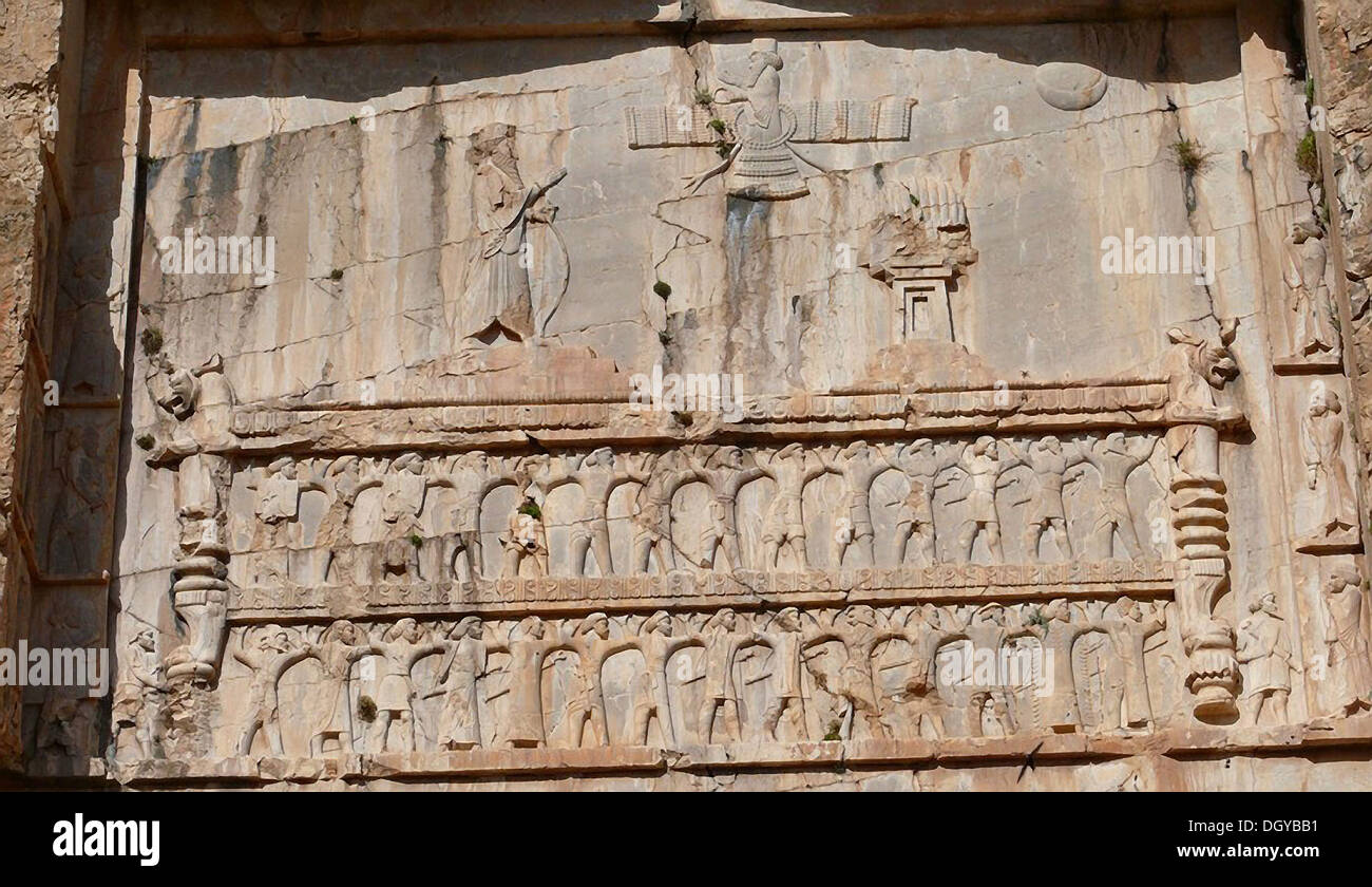 5653. The tomb of Darius I (c. 522–486 BC). located at Naqš-i Rustam, near Persepolis, The rock carved tomb has three panels its upper arm is a relief showing Darius I praying to the god Ahuramazda (who is shown as a winged disk). The twenty-eight people - Stock Image