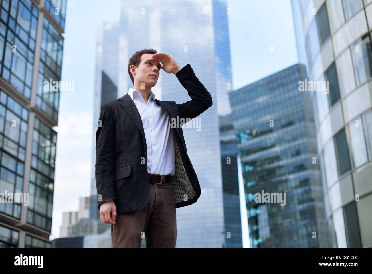 young business man looking forward on skyscrapers background - Stock Image