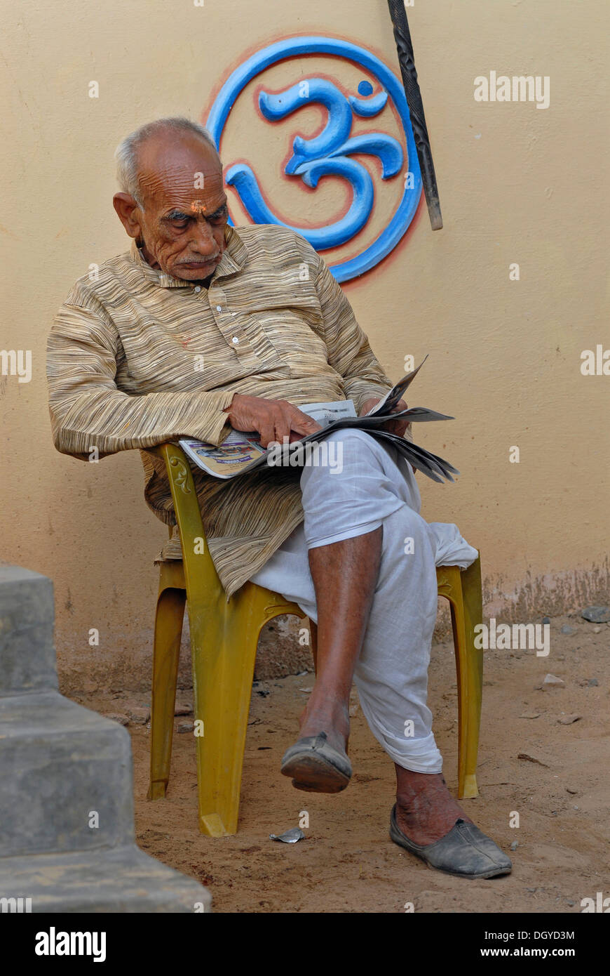 Man reading, in front of Om sign, Alsisar, Shekawati, Rajasthan, North India, India, Asia - Stock Image