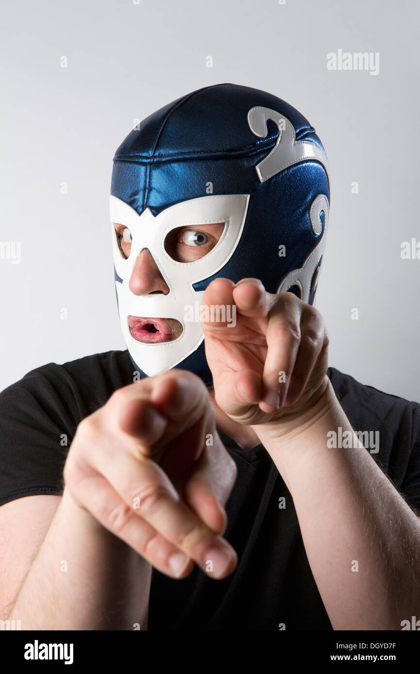 A man wearing a Lucha Libre wrestling mask and gesturing bizarrely with his hands - Stock Image