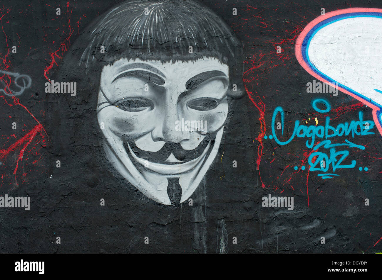 Graffiti of a man with an 'Anonymous' or 'Guy Fawkes' mask, symbol of the 'Occupy' protest movement against the power of the - Stock Image