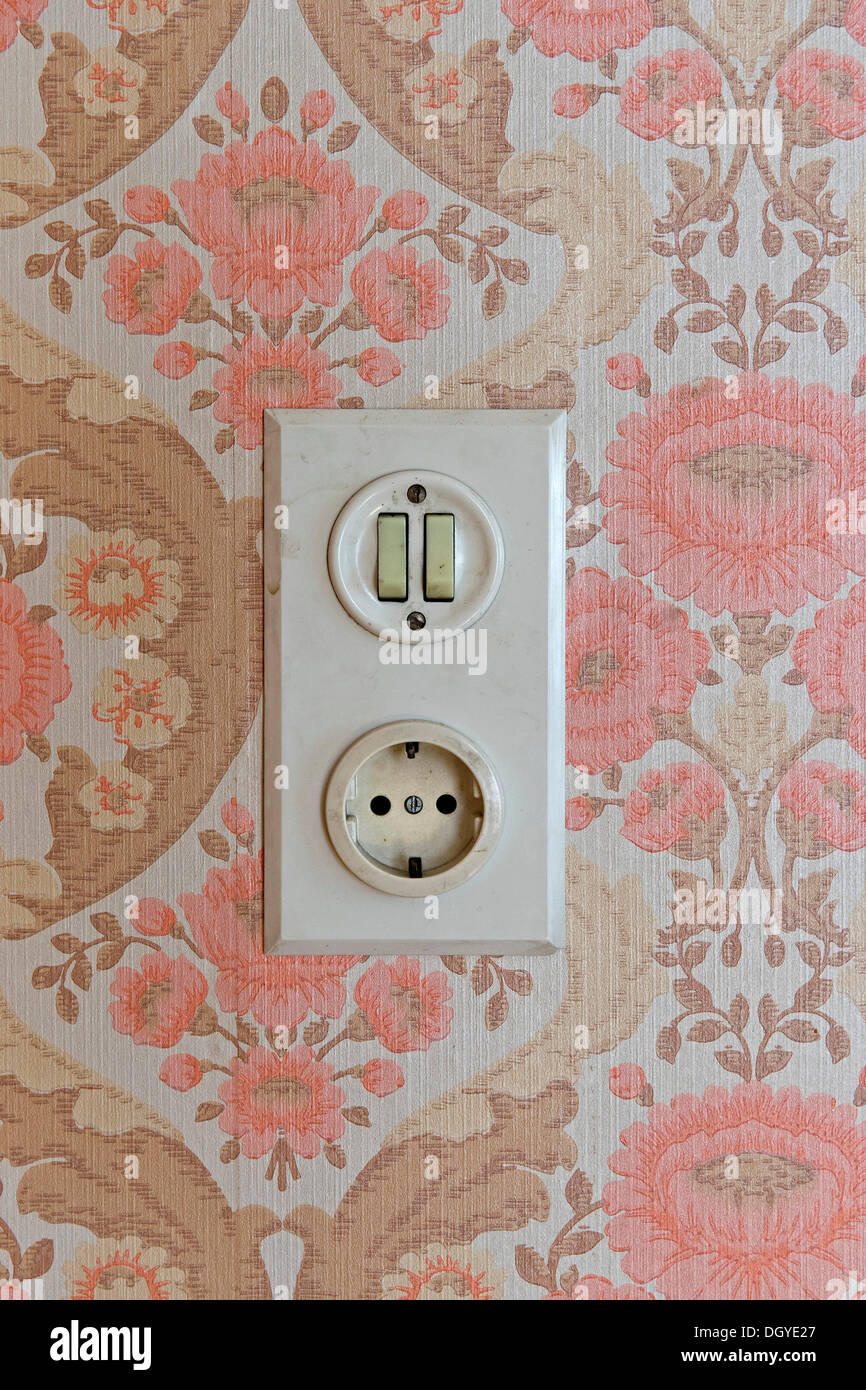 Old socket and light switch, wallpaper from the sixties, Stuttgart, Baden-Wuerttemberg - Stock Image