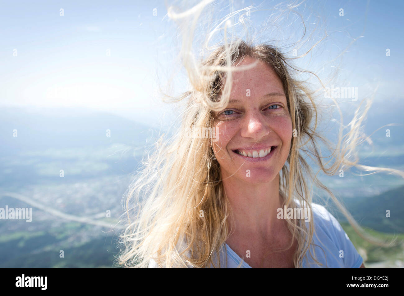 Woman, early 40s, with her hair blowing in the wind - Stock Image