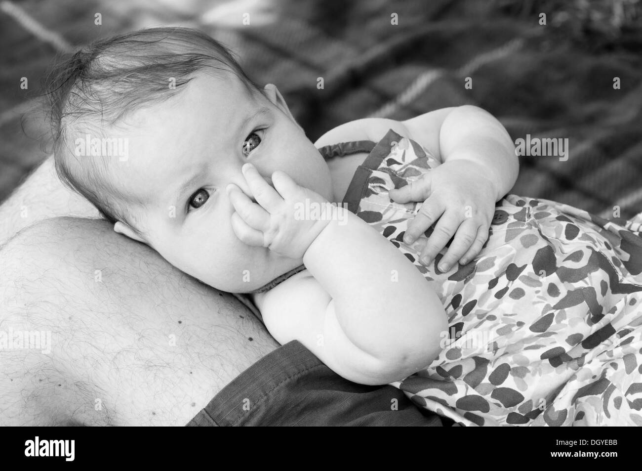 Close up black and white portrait of little baby girl sucking her thumb - Stock Image