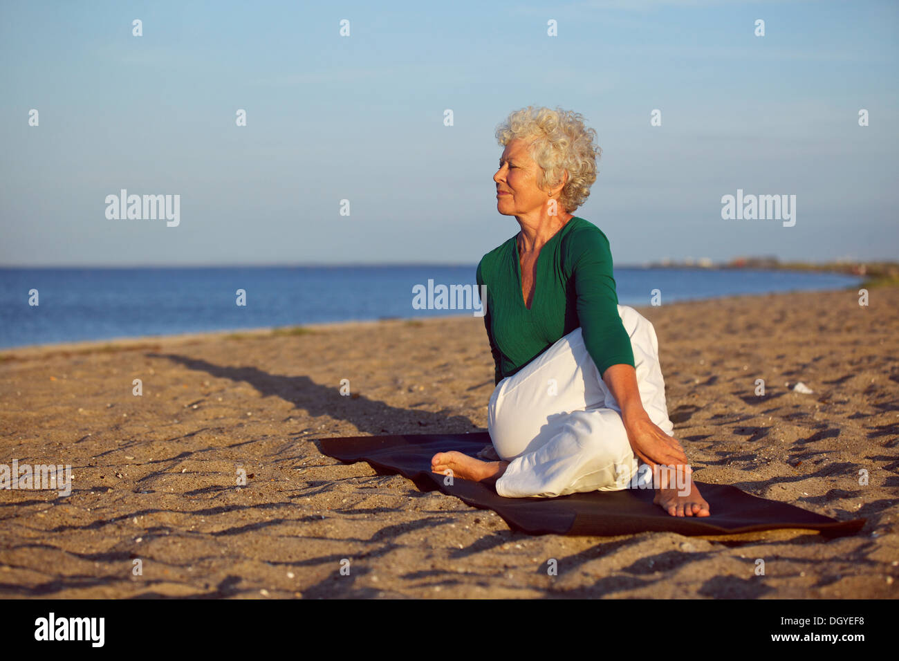 Senior woman performing a yoga routine on the beach. Elder woman doing stretching exercise on sandy beach with lots of copyspace - Stock Image