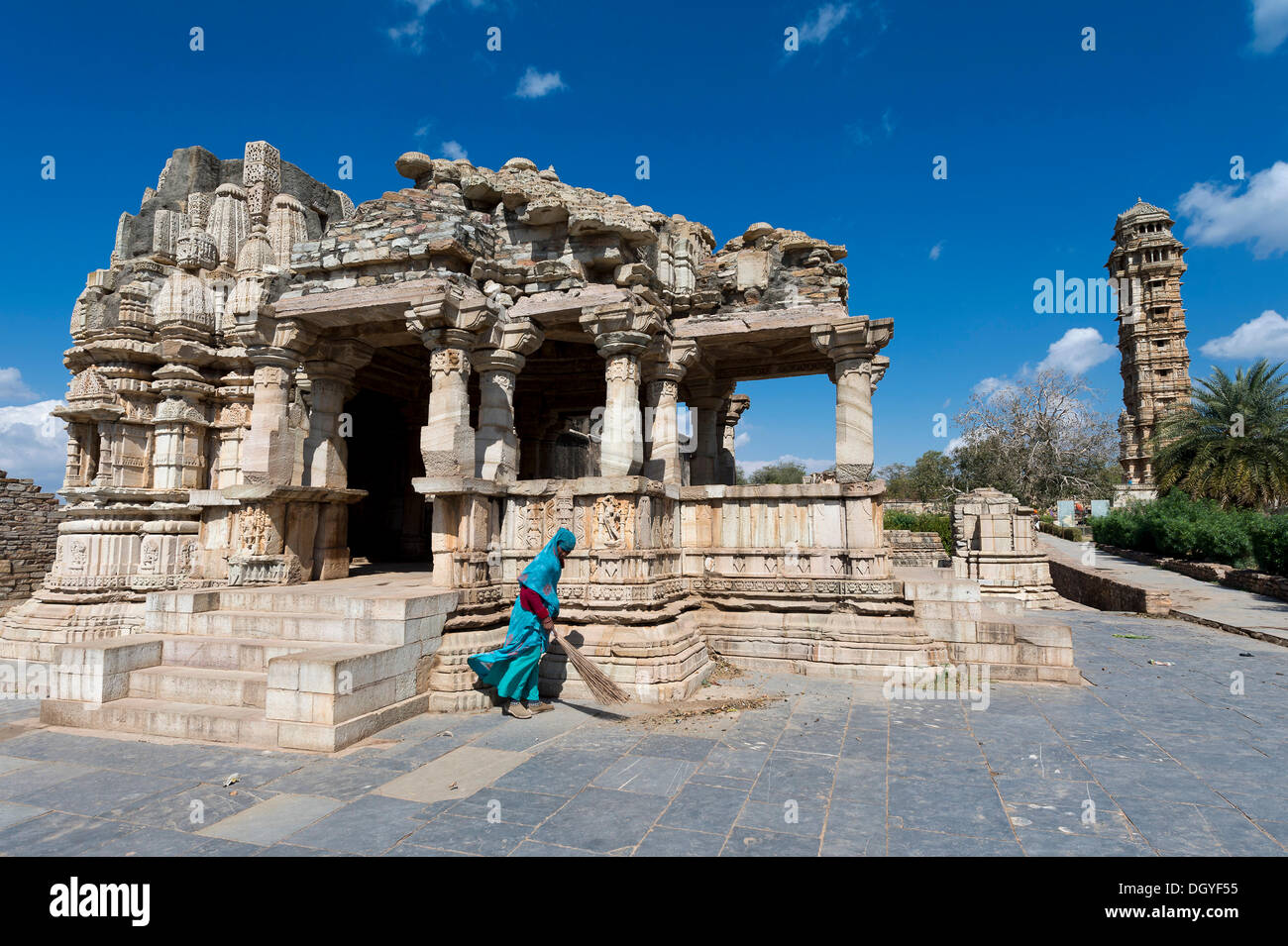 Woman sweeping the stone slabs in front of temple ruins, Vijaya Stambha, a victory tower built during the reign of Rana Kumbha - Stock Image
