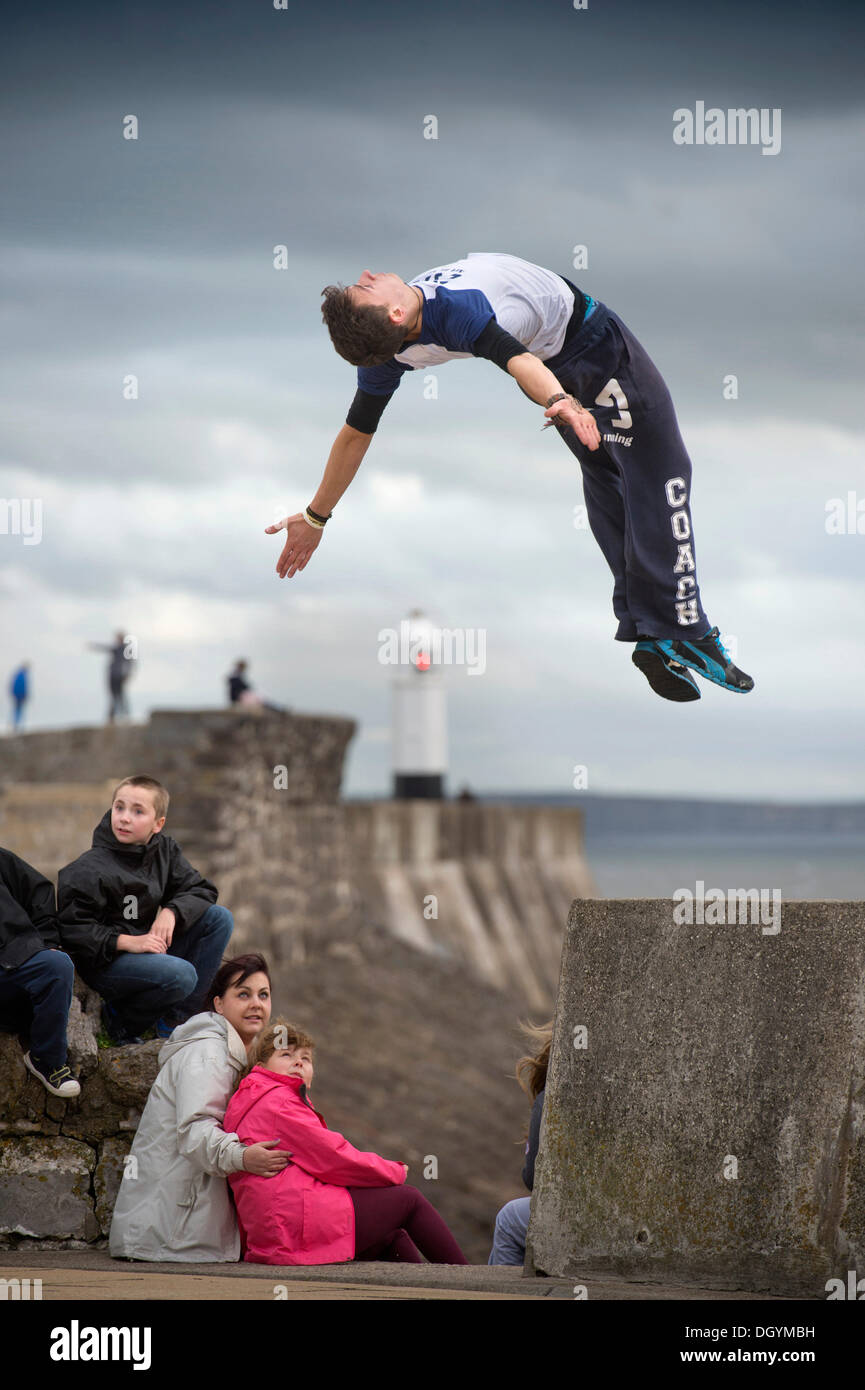 Porthcawl, South Wales, UK. 27th Oct, 2013. The parkour expert Andrew Cronin from Bridgend appears to anticipate the oncoming storm as he performs on the seafront at Porthcawl, South Wales (Saturday 26 Oct 2013)The storm, called St Jude, brought the windiest weather to hit the UK since 1987. © Adrian Sherratt/Alamy Live News - Stock Image