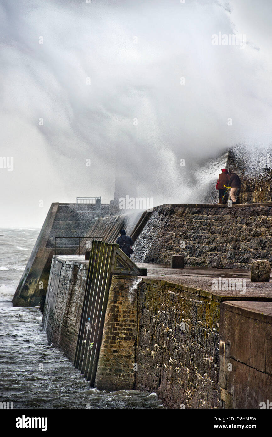 Porthcawl, South Wales, UK. 27th Oct, 2013. Sightseers are caught under a huge wave breaking over the sea wall at Porthcawl, South Wales (27 Oct 2013)The storm, called St Jude, brought the windiest weather to hit the UK since 1987. © Adrian Sherratt/Alamy Live News - Stock Image