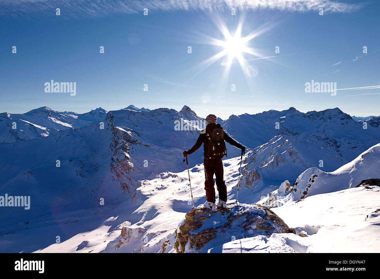 Winter sports enthusiast standing in front of the bright sun, Tux Alps, Tyrol, Austria, Europe - Stock Image