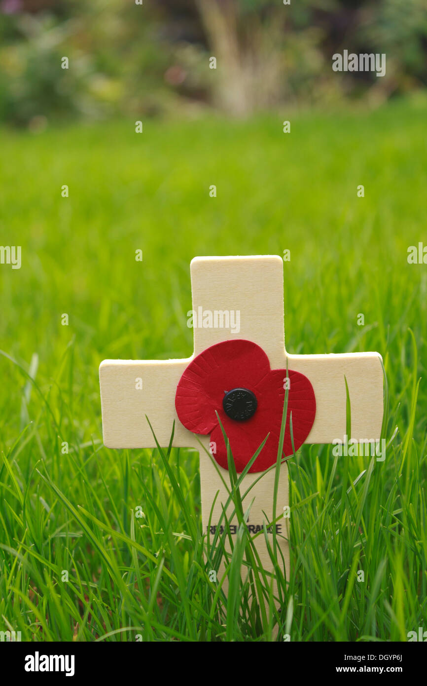 Remembrance Day wooden cross with red poppy on a green lawn - Stock Image
