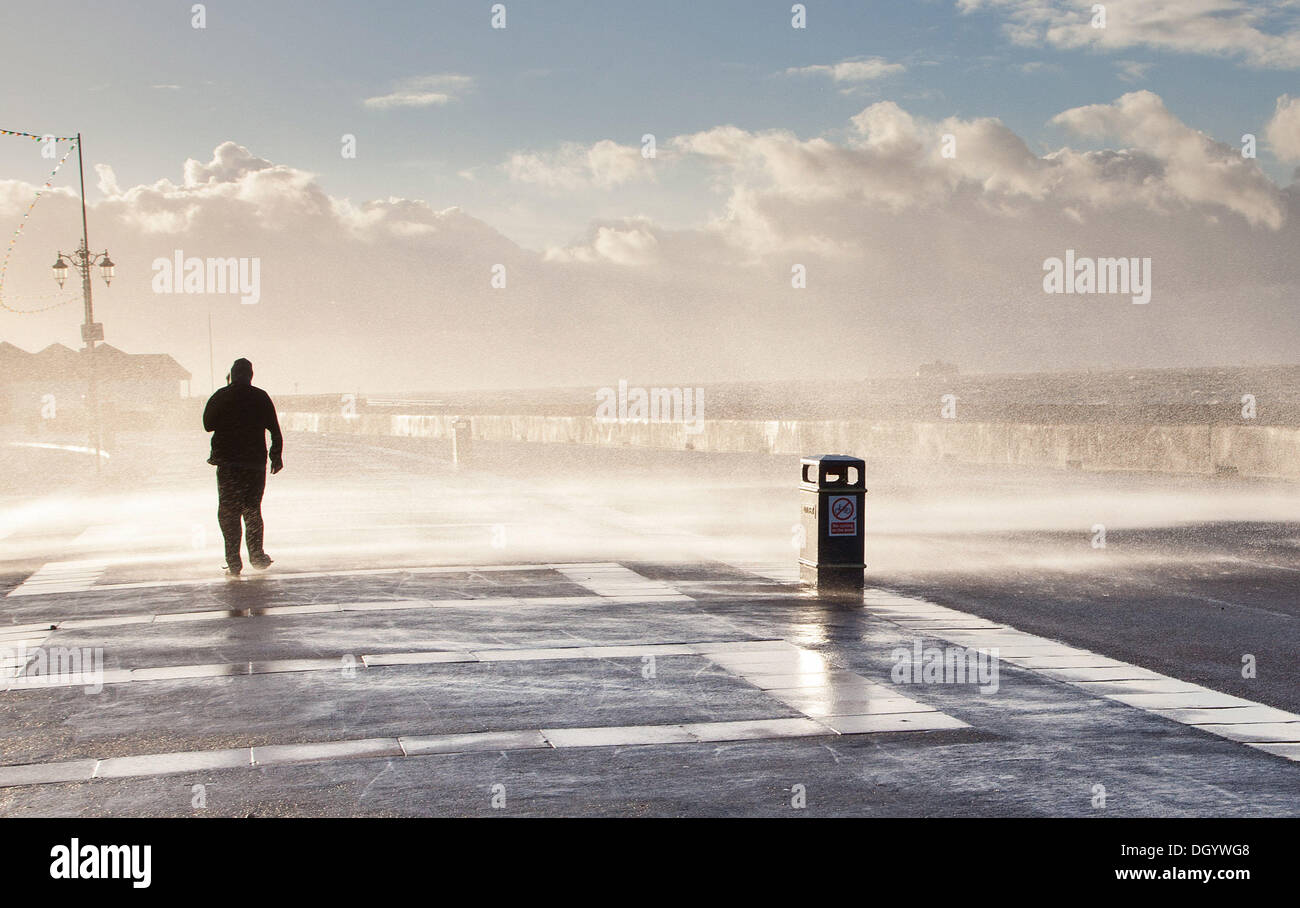 Portsmouth, Hampshire, UK. 28th Oct, 2013. Waves crash on a passer-by on Clarence Esplanade in Southsea, Hampshire. Stock Photo