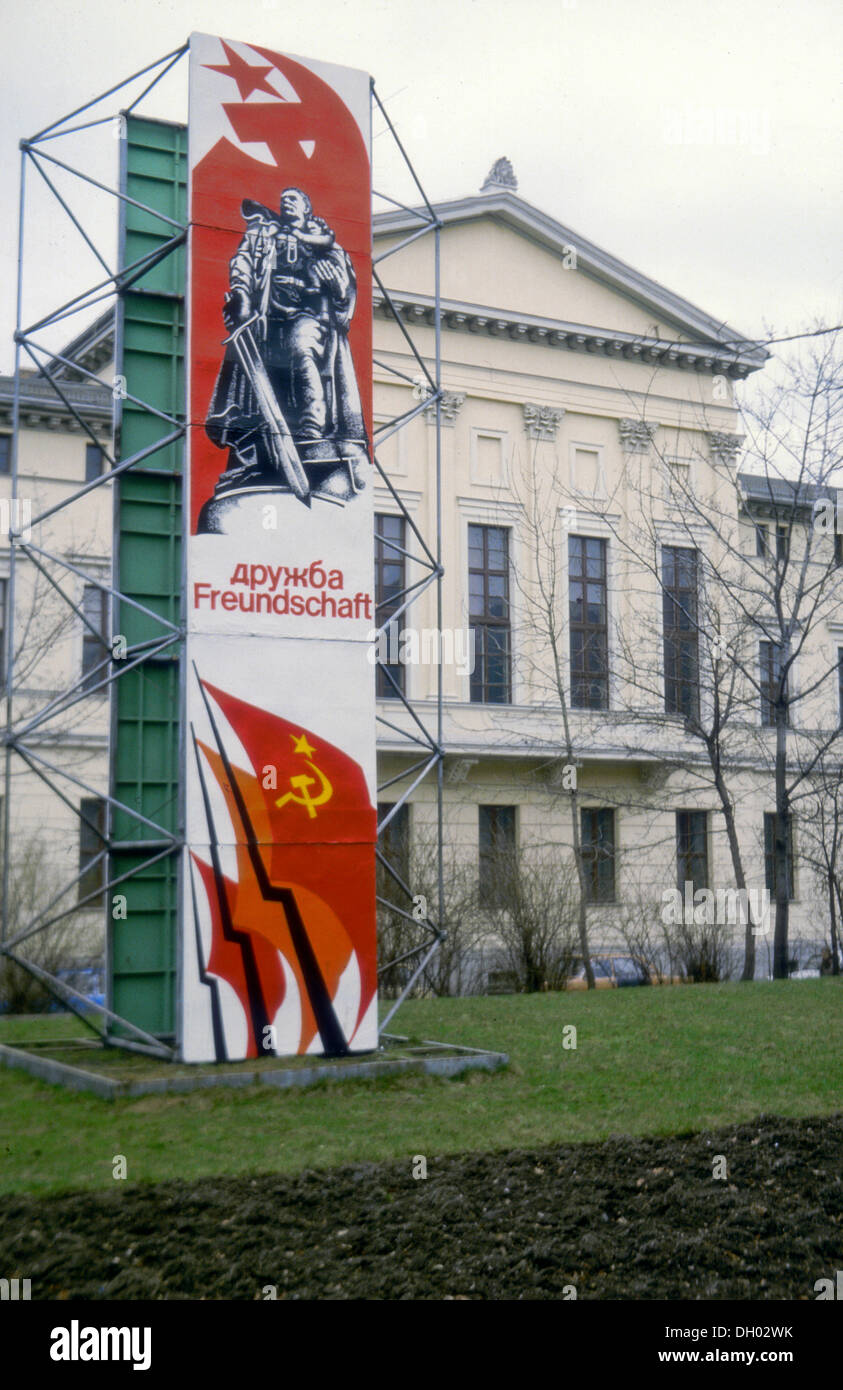 Socialist propaganda sign, Druzhba Freundschaft, Russian and German for friendship, with flags of the USSR in front of a - Stock Image