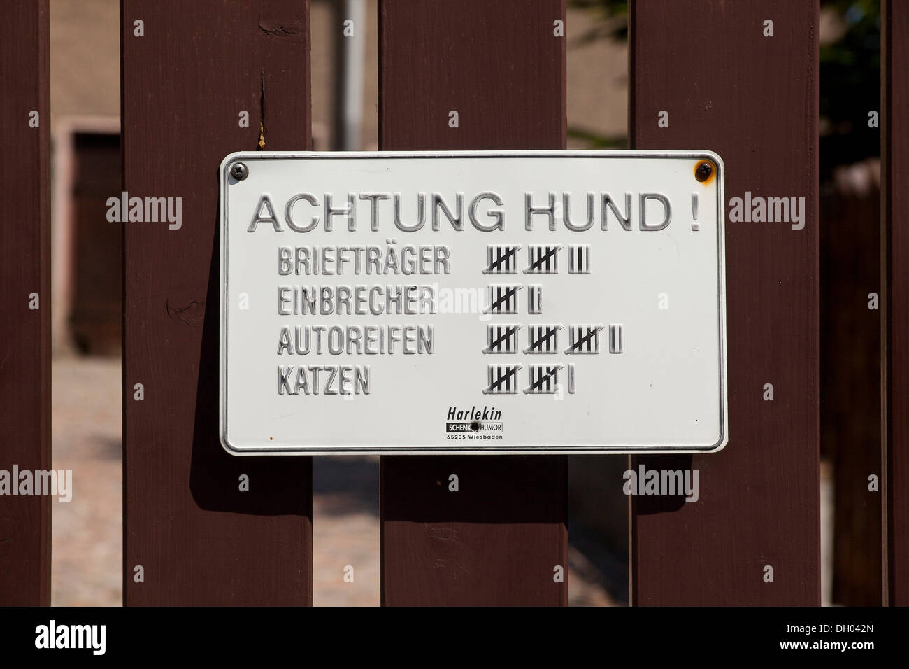Sign, lettering 'Achtung Hund!', German for 'Beware of the Dog!' with a tally sheet of its victims on a fence - Stock Image