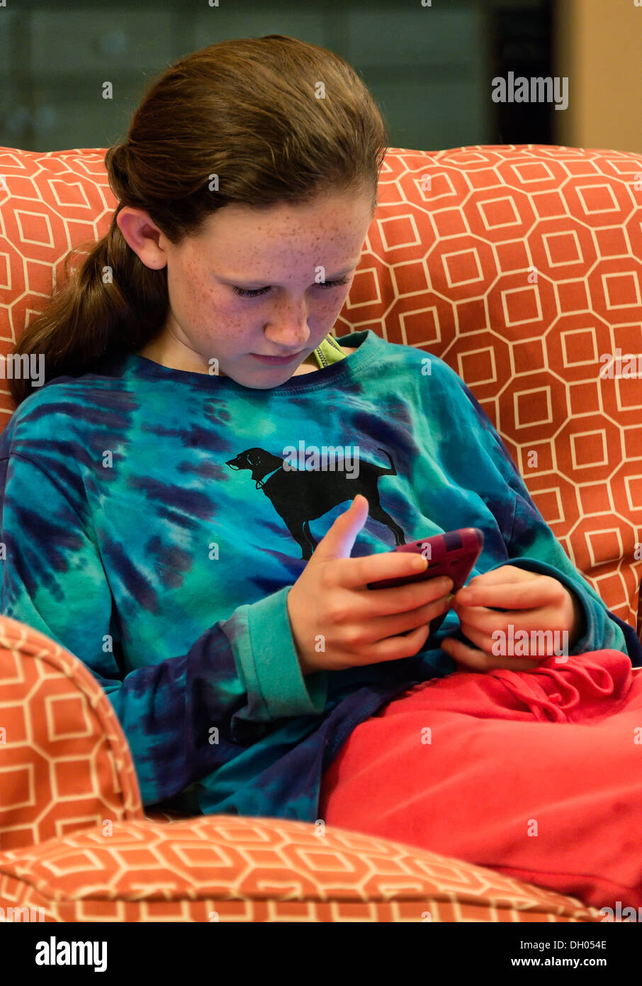 Twelve year old girl reading a text message on her mobile phone device. - Stock Image