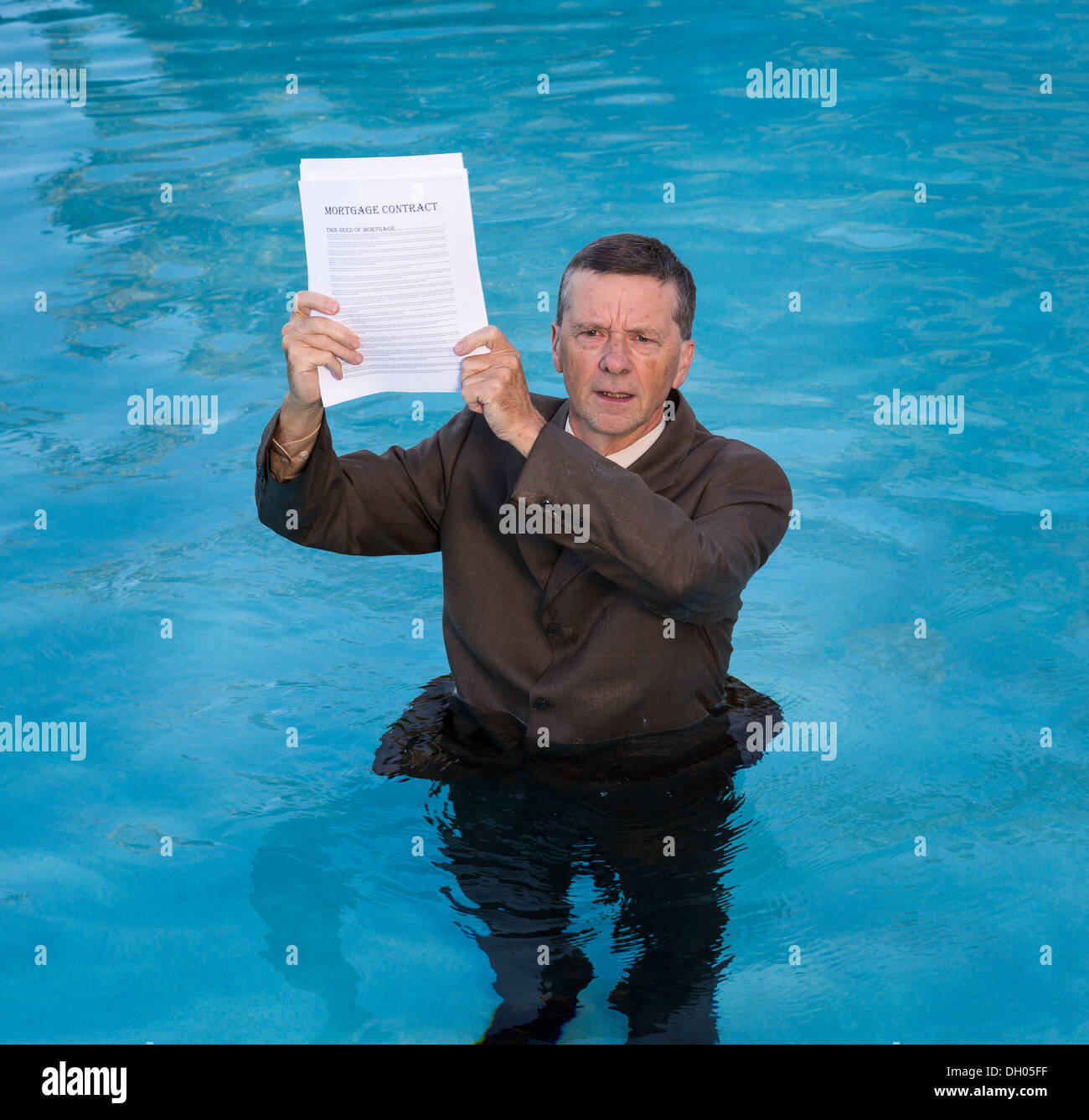 Businessman in suit in water worried about mortgage payments - Stock Image