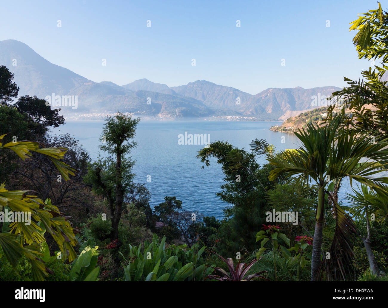 Sunrise at Lake Atitlan in Guatemala formed from volcano crater. Town of San Pedro La Laguna in distance - Stock Image